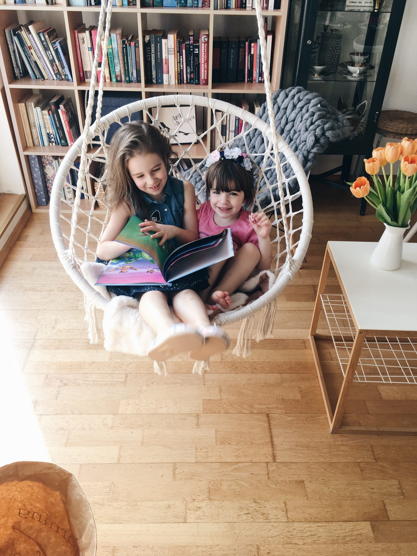Sretne djevojcice citaju knjigu ispred police za knjige