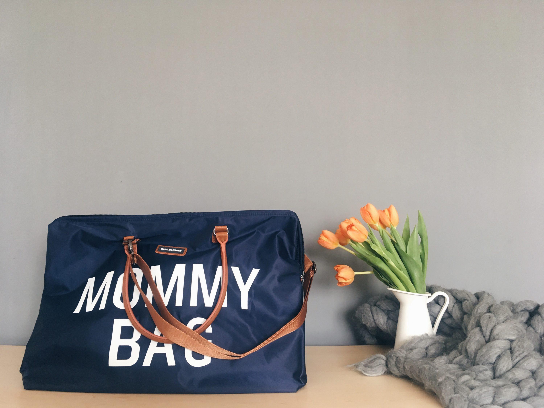 Torba za rodilište plave boje Mommy Bag pokraj tulipana u bijeloj vazii