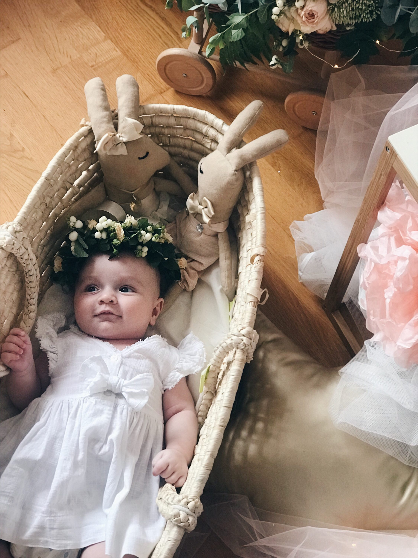 beba u košari sa cvjetnom krunom na glavi