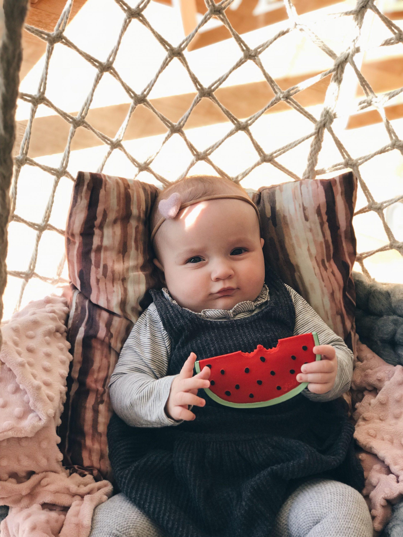 beba samodopadno gleda u kameru i drži lubenicu