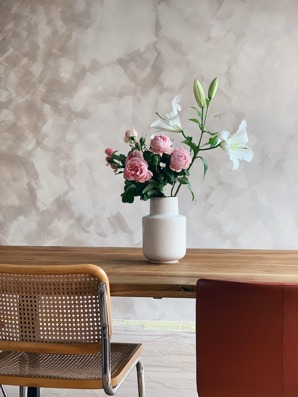 vaza s cvijećem ispred kalklitir zida