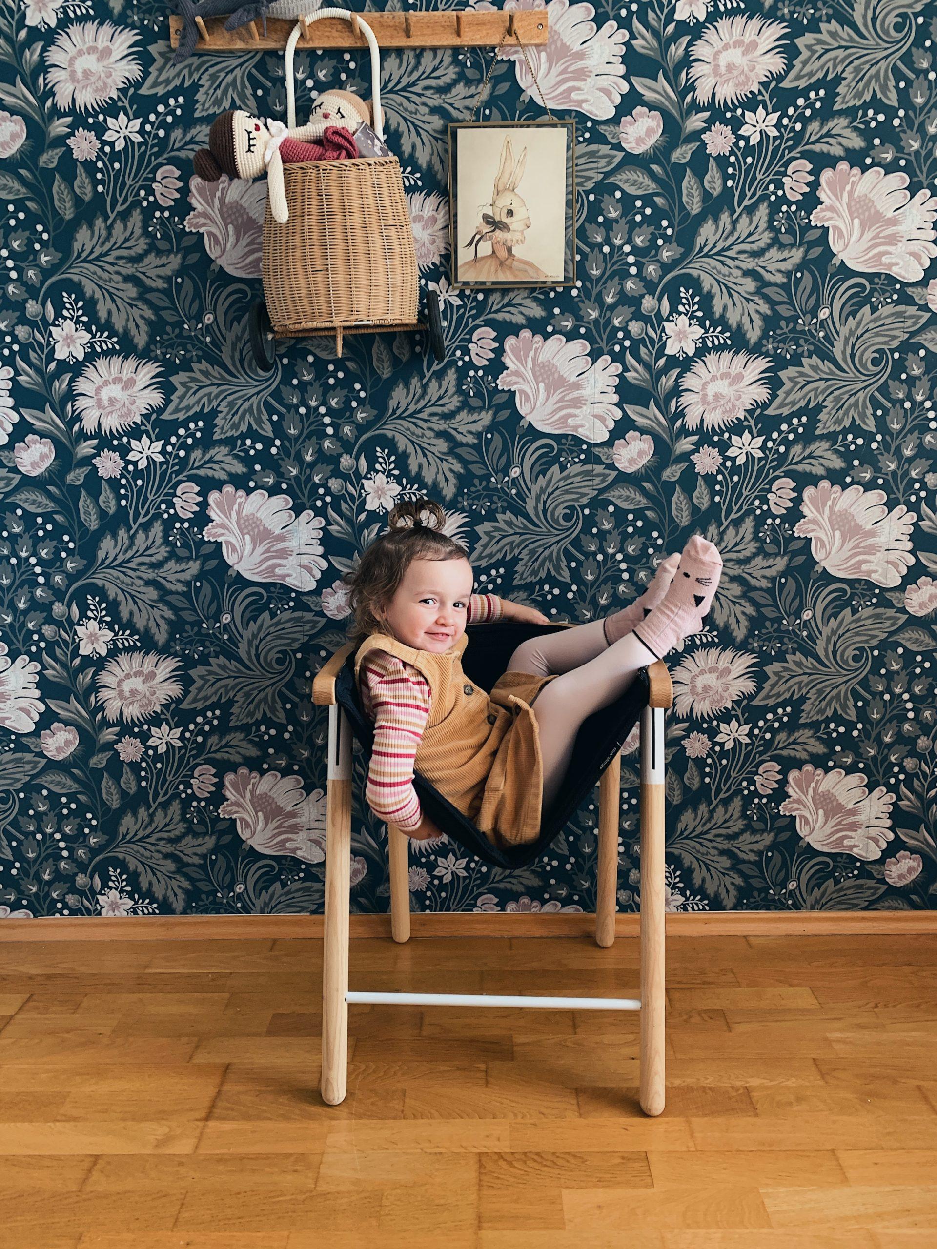 Mila u stolici ispred cvjetne tapete